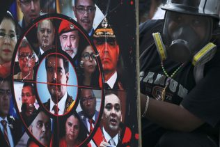 An anti-government protester holds a shield brandished with photos of President Nicolas Maduro, government officials and a gun sight, during clashes with security forces in Caracas, Venezuela, July 22, 2017. Fernando Llano | AP