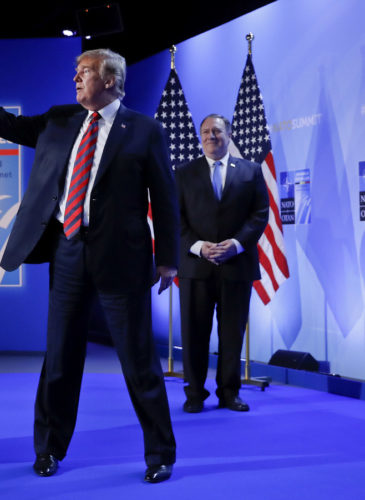Donald Trump waves as he walks off stage after holding a news conference before his departure at the NATO Summit in Brussels, Belgium, July 12, 2018. With Trump are Secretary of State Mike Pompeo, center, and National security adviser John Bolton, right. Pablo Martinez Monsivais | AP